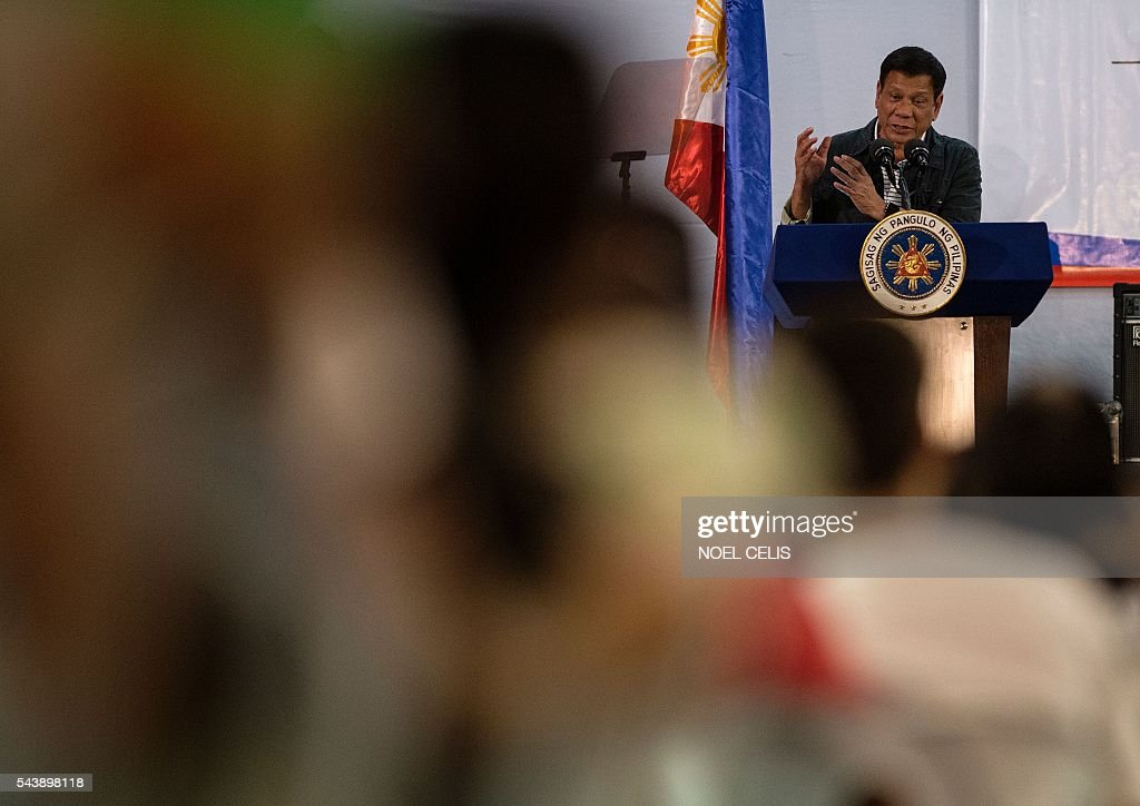 Philippine President Rodrigo Duterte gestures to the crowd he visited composed of families living in slum area of Manila on June 30, 2016. Authoritarian firebrand Rodrigo Duterte was sworn in as the Philippines' president on June 30, after promising a ruthless and deeply controversial war on crime would be the main focus of his six-year term. / AFP / NOEL