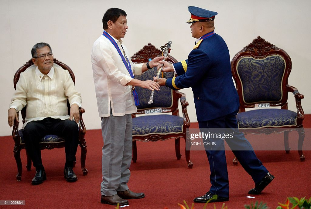 Philippine President Rodrigo Duterte (C) hands a saber to Philippine National Police (PNP) chief Ronald Bato Dela Rosa (R) during Dela Rosa's Assumption of Command Ceremony at the Camp Crame in Manila on July 1, 2016. Authoritarian firebrand Rodrigo Duterte was sworn in as the Philippines' president on June 30, after promising a ruthless and deeply controversial war on crime would be the main focus of his six-year term. / AFP / NOEL