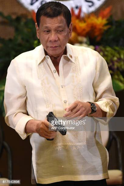 Philippine President Rodrigo Duterte holds a 45 caliber handgun one of 3000 units handed over during a ceremonial turnover to the military at...