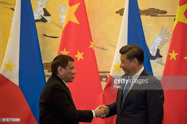Philippine President Rodrigo Duterte left and Chinese President Xi Jinping shakes hands after a signing ceremony on October 20 2016 in Beijing China...