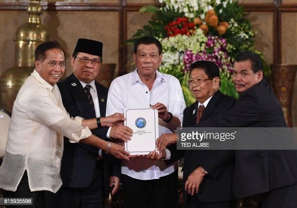 Philippine President Rodrigo Duterte poses with Secretary of the Peace Process Jesus Dureza AlHajj Murad chairman of Moro Islamic Liberation Front...