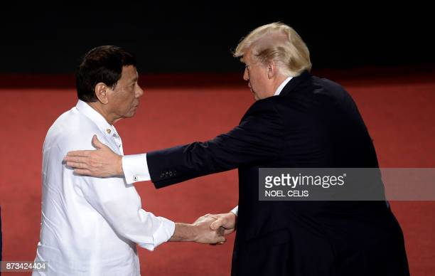 TOPSHOT Philippine President Rodrigo Duterte shakes hands with US President Donald Trump during the 31st Association of Southeast Asian Nations...