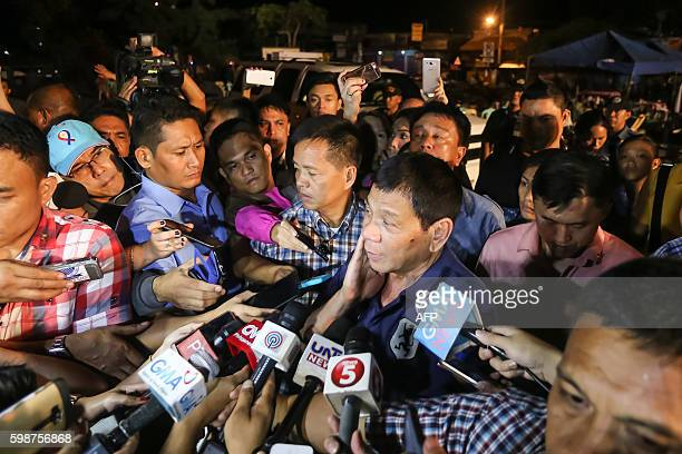 Philippine President Rodrigo Duterte speaks to members of the media as he visits the site of an explosion at a nigth market in Davao City in southern...