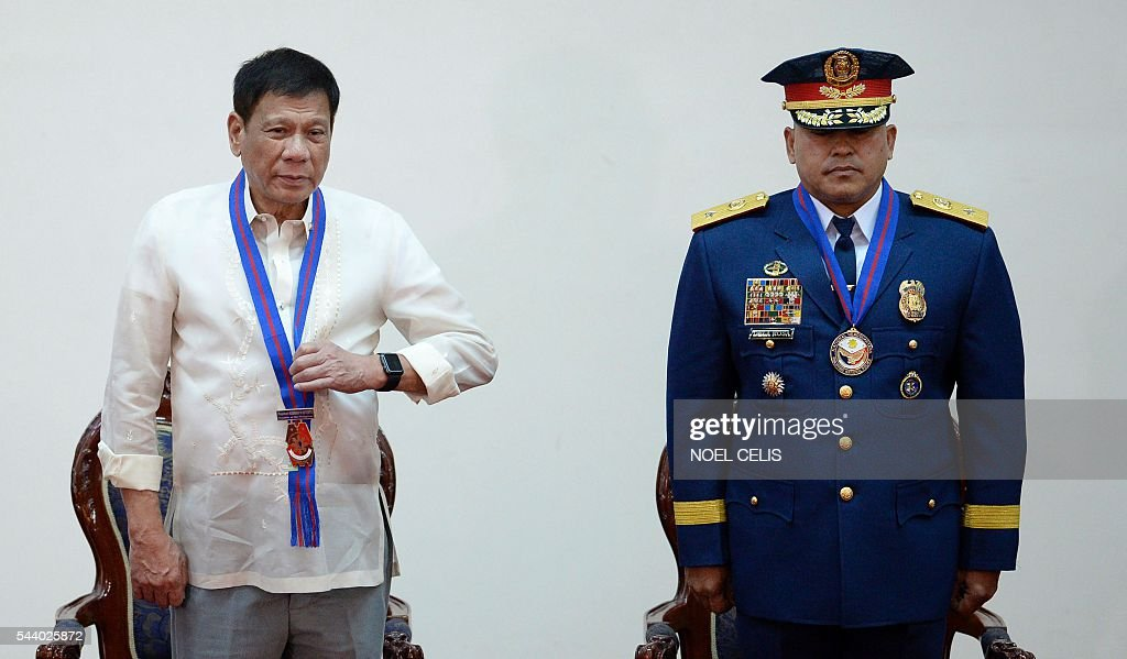 Philippine President Rodrigo Duterte (L) stand beside Philippine National Police (PNP) chief Ronald Bato Dela Rosa (R) during Dela Rosa's Assumption of Command Ceremony at the Camp Crame in Manila on July 1, 2016. Authoritarian firebrand Rodrigo Duterte was sworn in as the Philippines' president on June 30, after promising a ruthless and deeply controversial war on crime would be the main focus of his six-year term. / AFP / NOEL