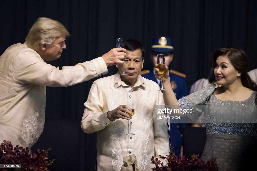 TOPSHOT - Philippine President Rodrigo Duterte (C) stands as his partner Honeylet Avancena (R) toasts US President Donald Trump during a special gala celebration dinner for the Association of Southeast Asian Nations (ASEAN) in Manila on November 12, 2017. World leaders arrive in the Philippines' capital for two days of summits beginning on November 13. /