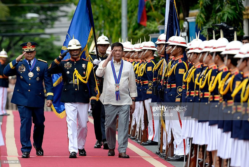 Philippine President Rodrigo Duterte (R) walks beside Philippine National Police (PNP) chief Ronald Bato Dela Rosa (L) during Dela Roasa's Assumption of Command Ceremony at the Camp Crame in Manila on July 1, 2016. Authoritarian firebrand Rodrigo Duterte was sworn in as the Philippines' president on June 30, after promising a ruthless and deeply controversial war on crime would be the main focus of his six-year term. / AFP / NOEL
