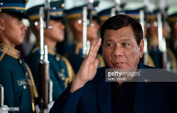 Philippine President Rodrigo Duterte walks past honour guards as he arrives at Manila international airport in Manila on May 24 after returning from...