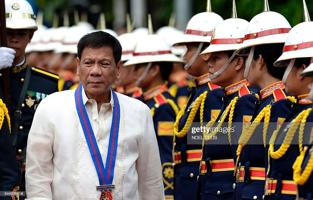 Philippine President Rodrigo Duterte walks past honour guards before Philippine National Police (PNP) chief Ronald Bato Dela Rosa's Assumption of Command Ceremony at the Camp Crame in Manila on July 1, 2016. Authoritarian firebrand Rodrigo Duterte was sworn in as the Philippines' president on June 30, after promising a ruthless and deeply controversial war on crime would be the main focus of his six-year term. / AFP / NOEL