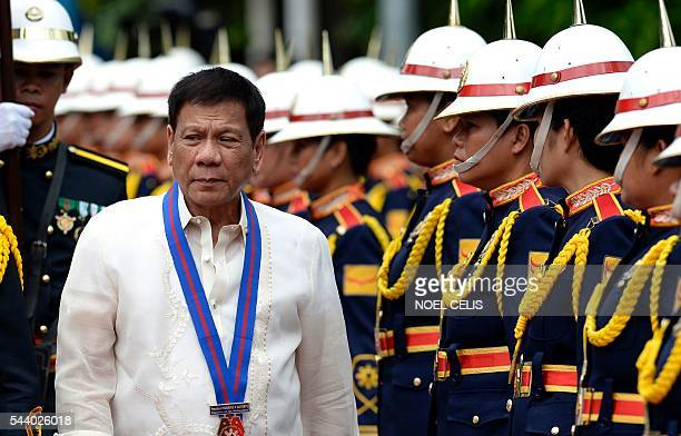 Philippine President Rodrigo Duterte walks past honour guards before Philippine National Police chief Ronald Bato Dela Rosa's Assumption of Command...