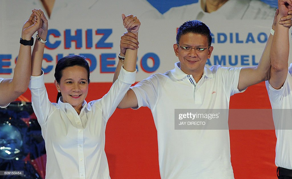 Philippine presidential candidate Grace Poe (L) and her running mate Senator Francis 'Chiz' Escudero raise their arms with their senatorial slate as they launch their campaigns for the May national elections in Manila on February 9, 2016. A cliffhanger race to lead the Philippines began February 9, with the adopted daughter of a dead movie star and a tough-talking politician who claims to kill criminals among the top contenders. AFP PHOTO / Jay DIRECTO / AFP / JAY DIRECTO