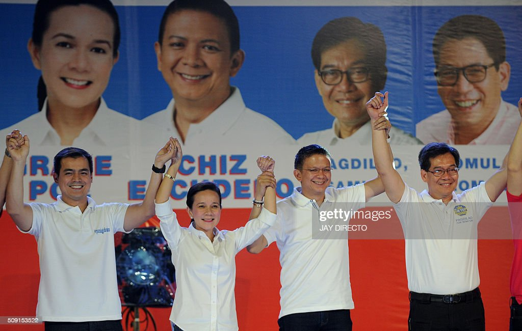 Philippine presidential candidate Grace Poe (2nd-L) and her running mate Senator Francis 'Chiz' Escudero (2nd-R) raise their arms with their senatorial slate as they launch their campaigns for the May national elections in Manila on February 9, 2016. A cliffhanger race to lead the Philippines began February 9, with the adopted daughter of a dead movie star and a tough-talking politician who claims to kill criminals among the top contenders. AFP PHOTO / Jay DIRECTO / AFP / JAY DIRECTO