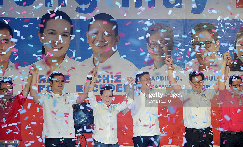 Philippine presidential candidate Grace Poe (3rd-L) and her running mate Senator Francis 'Chiz' Escudero (3rd-R) raise their arms with their senatorial slate as they launch their campaigns for the May national elections in Manila on February 9, 2016. A cliffhanger race to lead the Philippines began February 9, with the adopted daughter of a dead movie star and a tough-talking politician who claims to kill criminals among the top contenders. AFP PHOTO / Jay DIRECTO / AFP / JAY DIRECTO