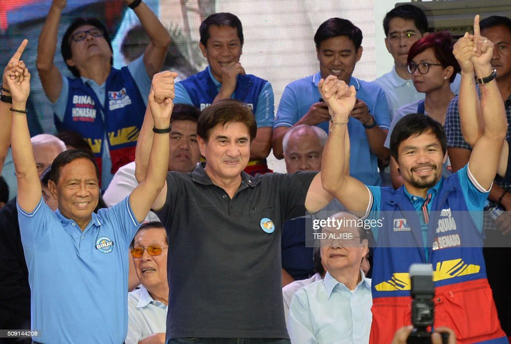 Philippine presidential candidate Jejomar Binay (L), who is leader of the opposition and current Philippine vice president, gestures onstage with his vice-presidential candidate Senator Gringo Honasan (C) plus senatorial candidate and boxing icon Manny Pacquiao (R) during their party's proclamation rally in Manila on February 9, 2016. A cliffhanger race to lead the Philippines began February 9 with the adopted daughter of a dead movie star and a tough-talking politician who claims to kill criminals among the top contenders. AFP PHOTO / TED ALJIBE / AFP / TED ALJIBE
