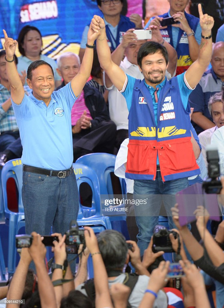 Philippine presidential candidate Jejomar Binay (L), who is leader of the opposition and current Philippine vice president, gestures to supporters with senatorial candidate and boxing icon Manny Pacquiao during his party's proclamation rally in Manila on February 9, 2016. A cliffhanger race to lead the Philippines began February 9 with the adopted daughter of a dead movie star and a tough-talking politician who claims to kill criminals among the top contenders. AFP PHOTO / TED ALJIBE / AFP / TED ALJIBE