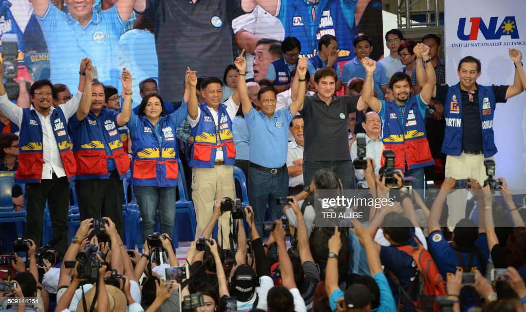 Philippine presidential candidate Jejomar Binay (4th R), who is leader of the opposition and current Philippine vice president, gestures onstage with his vice-presidential candidate Senator Gringo Honasan (3rd R), and senatorial line up led by boxing icon Manny Pacquiao (2nd R) raise their hands during their party's proclamation rally in Manila on February 9, 2016. A cliffhanger race to lead the Philippines began February 9 with the adopted daughter of a dead movie star and a tough-talking politician who claims to kill criminals among the top contenders. AFP PHOTO / TED ALJIBE / AFP / TED ALJIBE