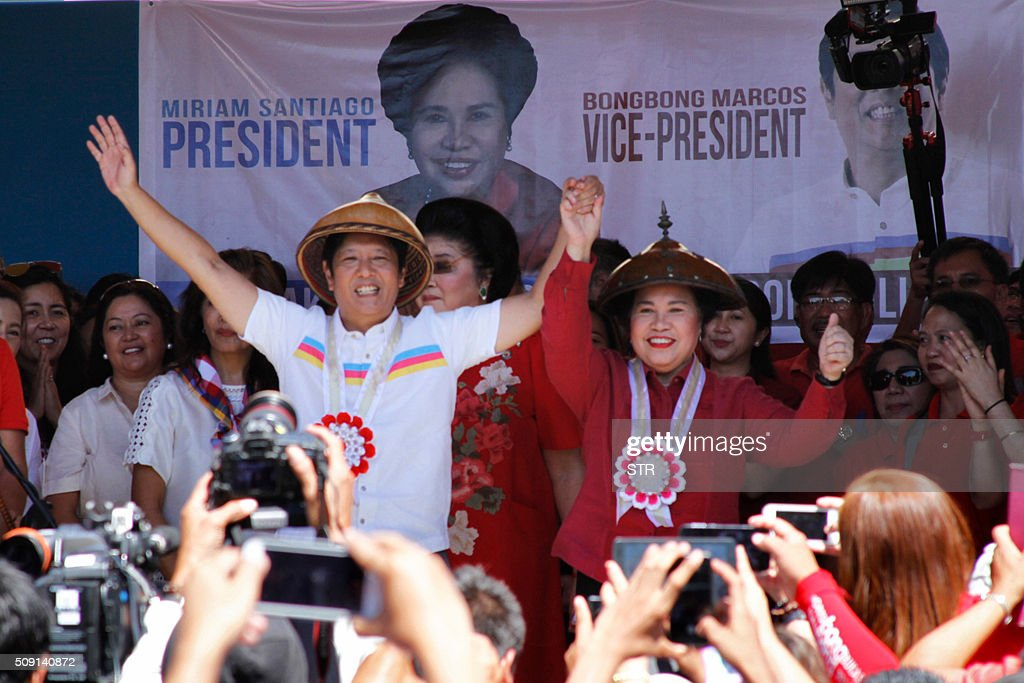 Philippine presidential candidate Miriam Santiago (centre R) and vice-presidential candidate Ferdinand Marcos Jr. (centre L), the son of late dictator Ferdinand Marcos, gesture to supporters onstage during a campaign rally in Batac town in Ilocos Norter province, north of Manila on February 9, 2016, at the start of the political campaign for the May 10 national elections. AFP PHOTO / AFP / STR