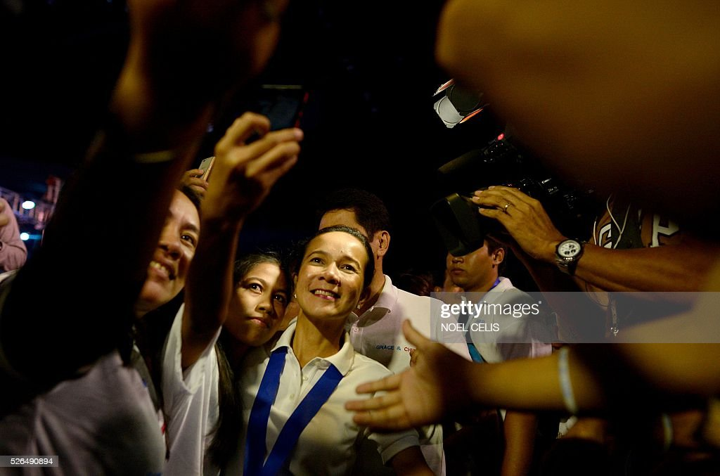 Philippine Presidential candidate Senator Grace Poe takes a selfie with supporters during a campaign rally in Manila on April 30, 2016. Poe is second to presidential front-runner and 'anti-crime firebrand' Mayor Rodrigo Duterte in a latest survey. / AFP / NOEL