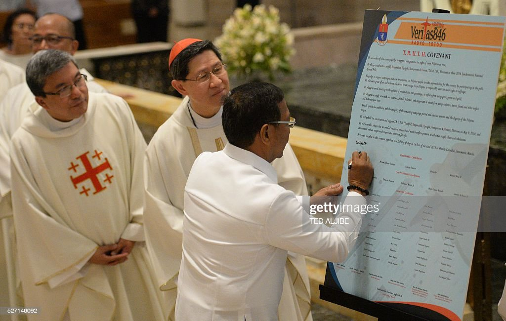 Philippine Presidential candidate VicePresident Jejomar Binay signs the covenant for a clean election during a ceremony inside the Manila cathedral...