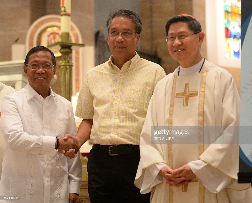 Philippine Presidential candidates VicePresident Jejomar Binay and former interior secretary Mar Roxas shake hands next to Roman Catholic Cardinal...
