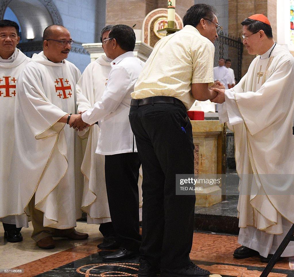 Philippine Presidential candidates VicePresident Jejomar Binay and former interior secretary Mar Roxas shake hands with Roman Catholic Cardinal Luis...