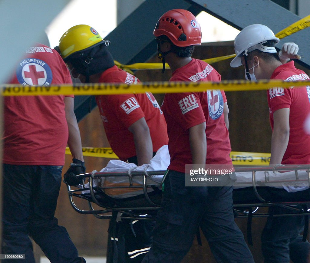 Philippine Red Cross workers transport a body after an accident at a power plant in Manila on February 4, 2013. Five workers were killed and dozen injured when a scaffolding collapsed while they were repairing a smokestack, according to rescuers. AFP PHOTO / Jay DIRECTO