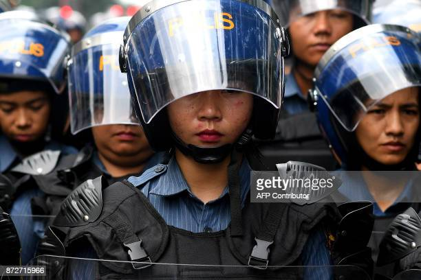 Philippine RiotPolicewomen stand guard during a protest against US President Donald Trump ahead of the 31st Association of Southeast Asian Nations...