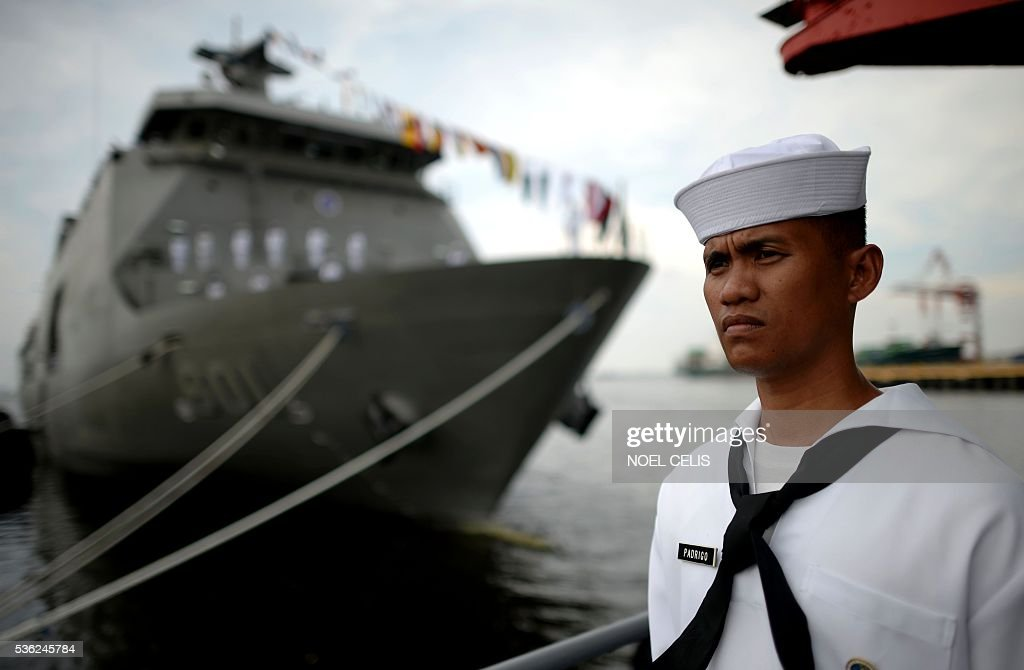 A Philippine sailor stands guard in front of the newly-commissioned BRP Tarlac (LD-601), an amphibious landing dock vessel, during the Philippine Navy's 118th anniversary celebrations at Pier 13, South Harbor, in Manila on June 1, 2016. The 118th anniversary of the Philippine Navy was celebrated with the simultaneous commissioning of the BRP Tarlac, the newest ship in the navy's inventory. / AFP / NOEL