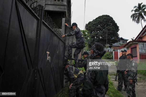 Philippine security forces climbing up a locked gate to inspect inside empty houses within the vicinity of a military camp and a hospital for guns...