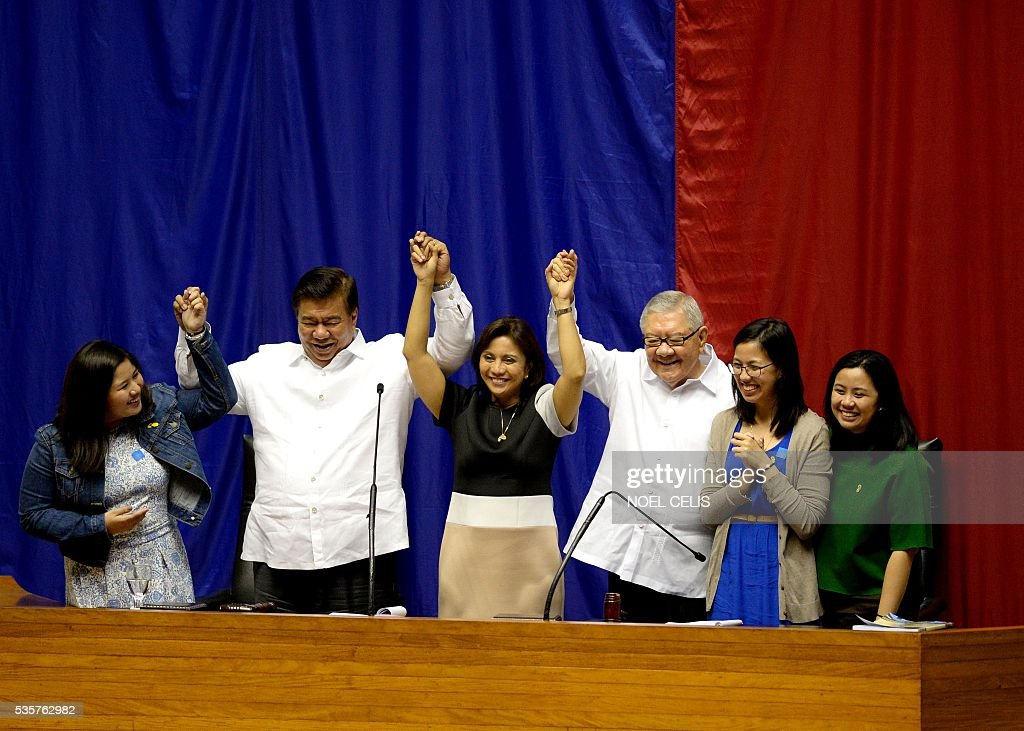 Philippine Senate president Frank Drilon (2nd L) and House speaker Feliciano Belmonte (3rd R) raise the hands of vice president-elect Leni Robredo (3rd L) as Robredo's daughters Jessica Marie (L), Janine Patricia (2nd R), and Jillian Therese (R) look on during Robredo's proclamation as vice president at the Session Hall of the House of Representatives in Manila on May 30, 2016. The Philippine parliament on May 30 proclaimed Rodrigo Duterte the nation's next president following his landslide election win this month, but he snubbed the high-profile event. Leni Robredo, who was declared the winner of the vice president election and a member of outgoing president Benigno Aquino's Liberal Party, attended the event along with her family and supporters. CELIS