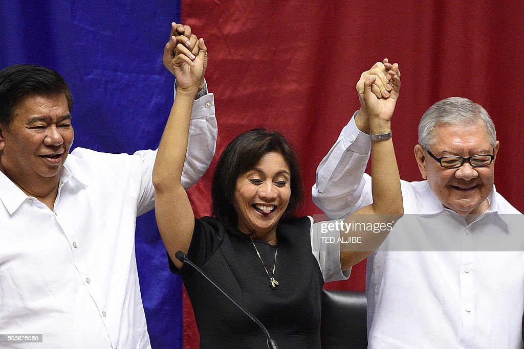 Philippine Senate president Frank Drilon (L) and House speaker Feliciano Belmonte (R) raise the hands of vice president-elect Leni Robredo as she reacts during her proclamation as vice president at the Session Hall of the House of Representatives in Manila on May 30, 2016. The Philippine parliament on May 30 proclaimed Rodrigo Duterte the nation's next president following his landslide election win this month, but he snubbed the high-profile event. Leni Robredo, who was declared the winner of the vice president election and a member of outgoing president Benigno Aquino's Liberal Party, attended the event along with her family and supporters. ALJIBE