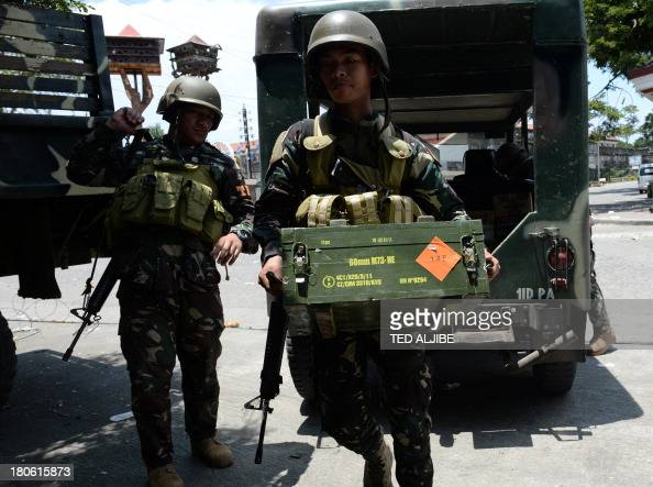 A Philippine soldier carries a case of ammunition at a hideout during a lull in fighting as a standoff between military troops and Muslim rebels...
