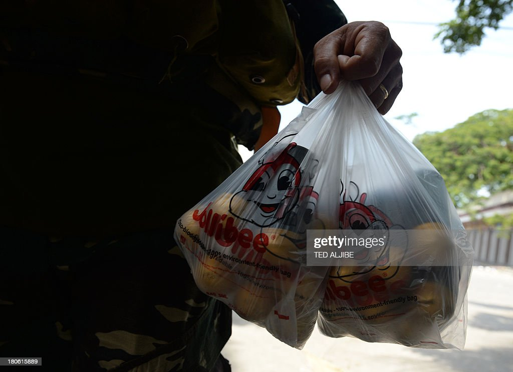 A Philippine soldier carries a plastic bag containing M-203 ammunition at a hideout during a lull in fighting as a stand-off between military troops and Muslim rebels enters its seventh day in Zamboanga, on the southern island of Mindanao on September 15, 2013. Philippine troops were on September 15 closing in on Muslim rebel positions and cutting off escape routes to end a week-long standoff that has left more than 60 people dead in the southern city of Zamboanga, officials said. AFP PHOTO / TED ALJIBE