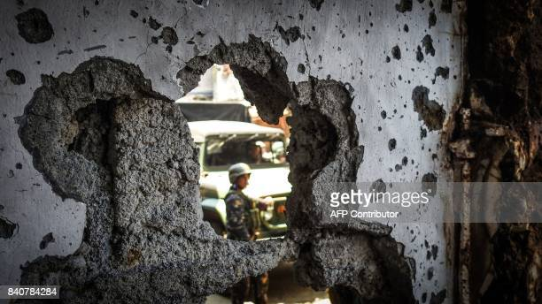 A Philippine soldier is seen past a hole in the wall of a damaged building in the Mapandi area of Marawi on the southern island of Mindanao on August...
