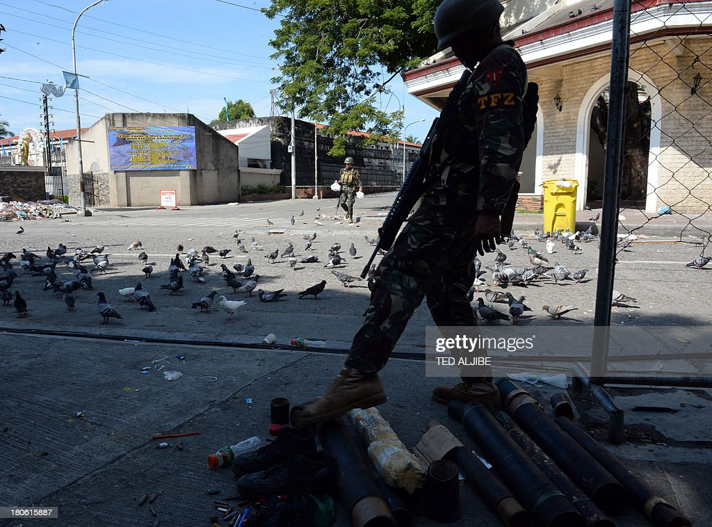 A Philippine soldier kicks empty mortar sheels recovered from a Muslim rebels hideout the night before during a stand-off between military troops and rebels in Zamboanga, on the southern island of Mindanao on September 15, 2013. Philippine troops were on September 15 closing in on Muslim rebel positions and cutting off escape routes to end a week-long standoff that has left more than 60 people dead in the southern city of Zamboanga, officials said.