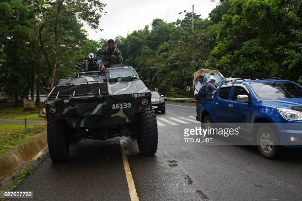 A Philippine soldier sits on an Armoured Personnel Carrier while residents fleeing from Marawi city drive past on a highway going to Marawi in Baloi...