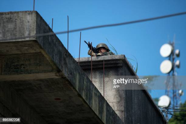 A Philippine soldier takes aim at militant positions from a building's rooftop in Marawi on the southern island of Mindanao on June 13 2017 Thousands...
