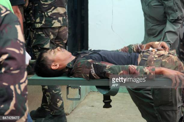 A Philippine soldier wounded in an ongoing clash with Islamist militants from the Abu Sayyaf group is carried on a stretcher as he arrives at a...