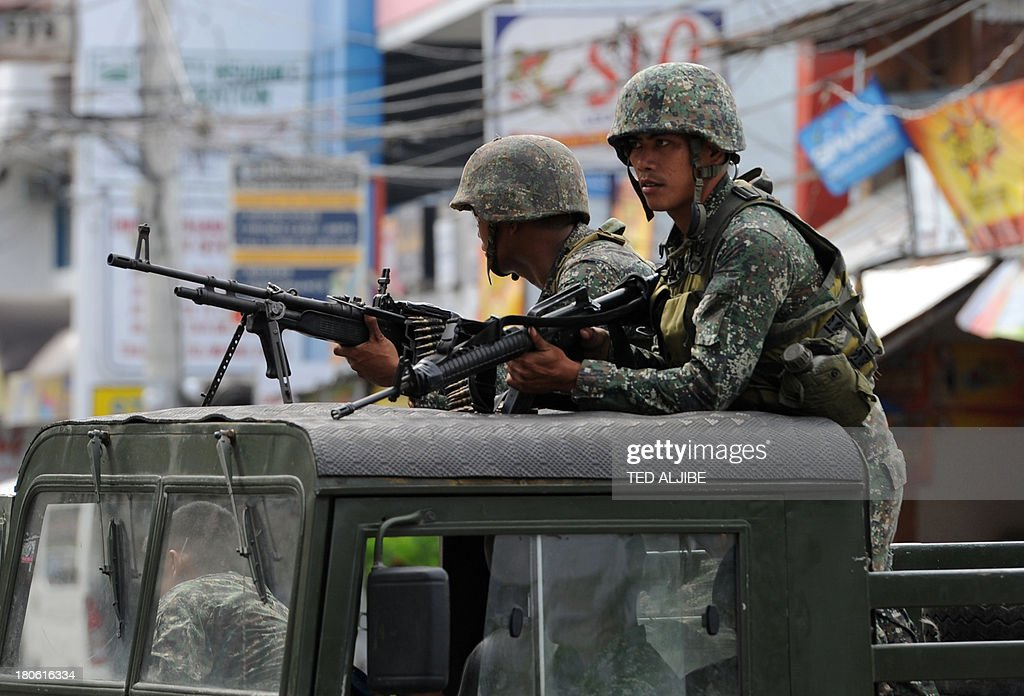 Philippine soldiers aboard a humvee stand guard during clearing operations against Muslim rebels as the standoff between military troops and the...