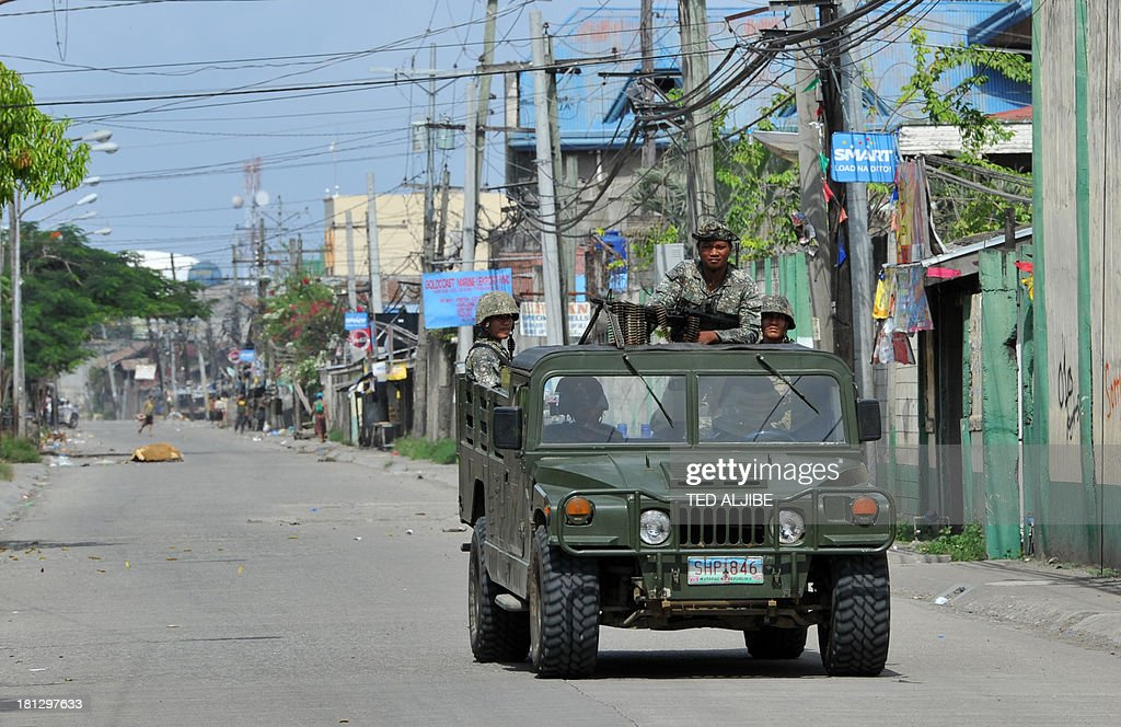 Philippine soldiers aboard a military jeep travel along a road near the site of the stand-off between government forces and the remnants of Muslim rebels in Zamboanga on the southern Philippine island of Mindanao on September 20, 2013. Philippine security forces killed eight Muslim rebels on September 20 as they hunted the remnants of a guerrilla force hiding in homes of a major city and believed to be holding hostages.