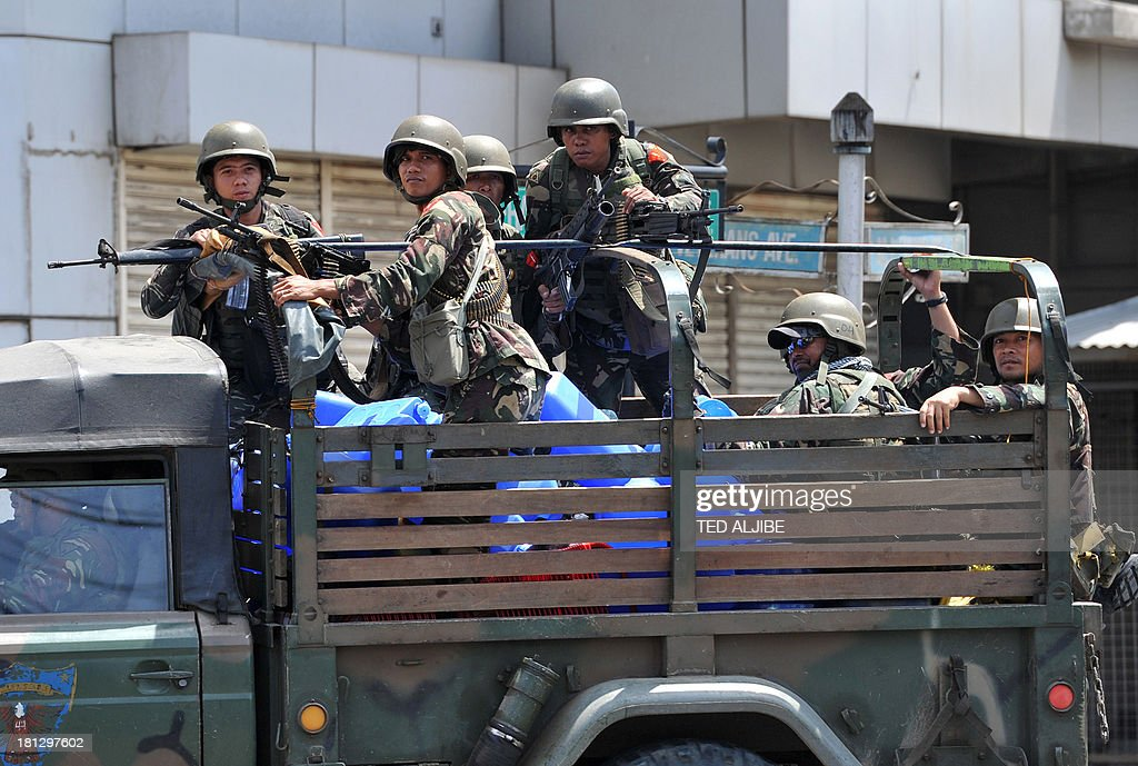 Philippine soldiers aboard a military truck patrol near the site of the stand-off between government forces and the remnants of Muslim rebels in Zamboanga on the southern Philippine island of Mindanao on September 20, 2013. Philippine security forces killed eight Muslim rebels on September 20 as they hunted the remnants of a guerrilla force hiding in homes of a major city and believed to be holding hostages. AFP PHOTO/TED ALJIBE