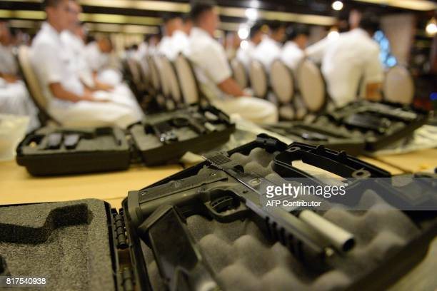 Philippine soldiers are seen past 45 caliber handguns ahead of a handover of some 3000 units of the weapons to the military at Malacanang Palace in...