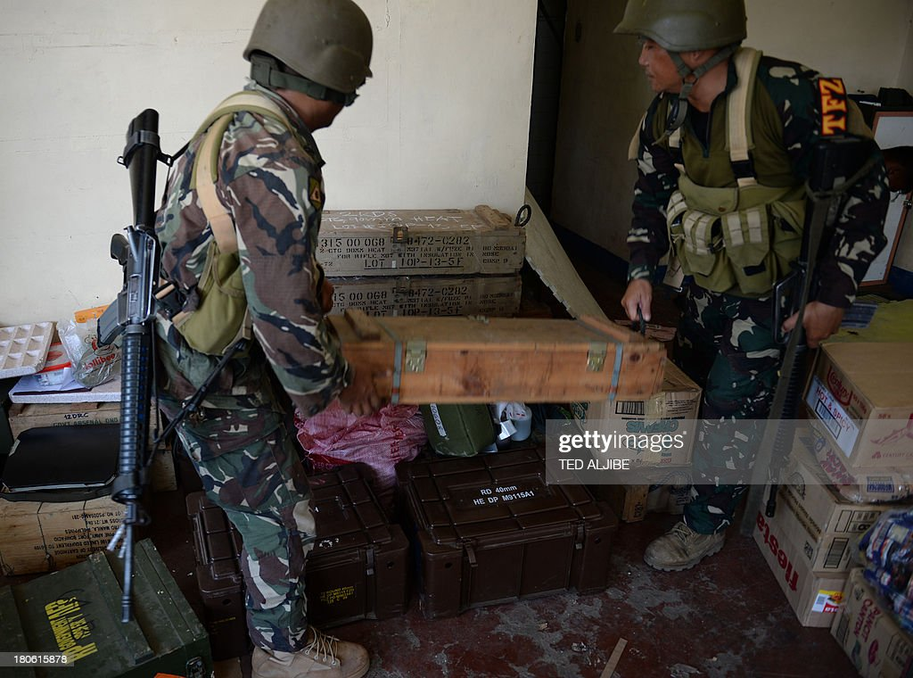 Philippine soldiers arrange ammunition in their hideout during a lull in fighting as a stand-off between military troops and Muslim rebels enters its seventh day in Zamboanga, on the southern island of Mindanao on September 15, 2013. Philippine troops were on September 15 closing in on Muslim rebel positions and cutting off escape routes to end a week-long standoff that has left more than 60 people dead in the southern city of Zamboanga, officials said. AFP PHOTO / TED ALJIBE