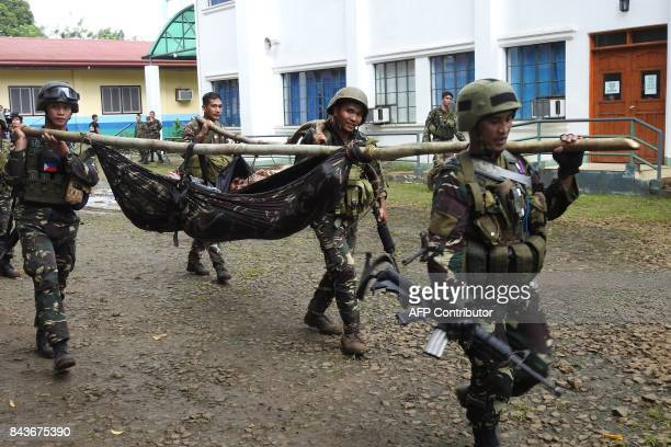 Philippine soldiers carry the bodies of members of the Abu Sayyaf group after an encounter in Jolo Sulu province on the southern island of Mindanao...