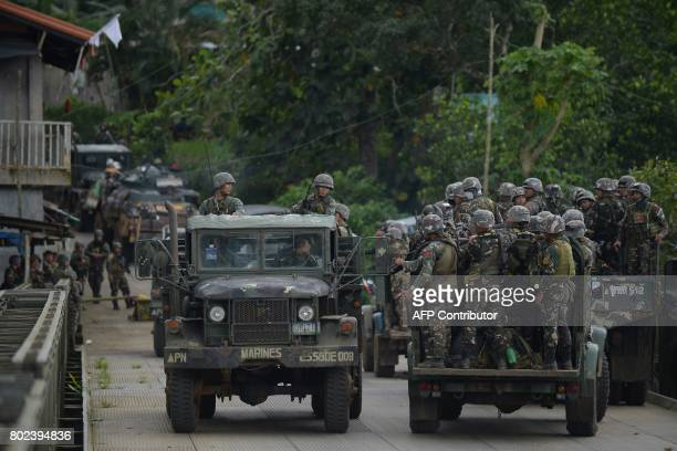 Philippine soldiers headed to the frontline look on at fellow Marines moving past in the outskirts of Marawi on the southern island of Mindanao on...