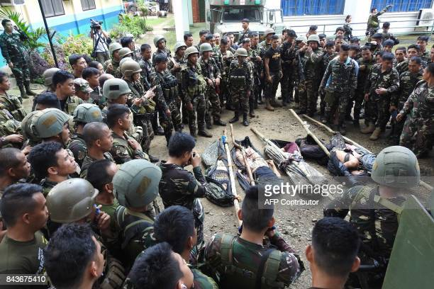 TOPSHOT Philippine soldiers look at the bodies of members of the Abu Sayyaf group after an encounter in Jolo Sulu province on the southern island of...