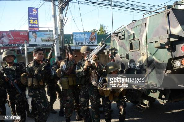 Philippine soldiers maneouver during an assault on Muslim rebel positions as the standoff enters its fifth day in Zamboanga City on September 13 2013...