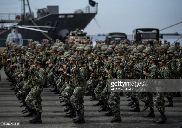 Philippine soldiers march as they arrive at the port of Manila on October 30 with some 500 personnel composed of marines sailors aviators and...