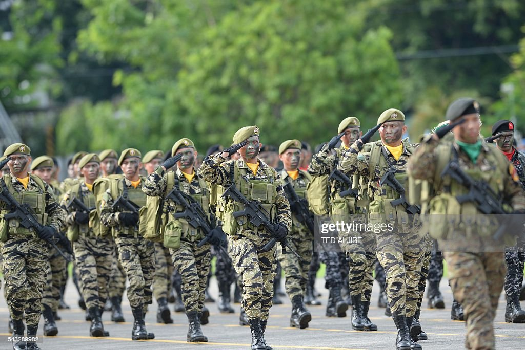 Philippine soldiers march during the testimonial parade for the outgoing president Benigno Aquino at the military headquarters in Manila on June 27, 2016. Aquino called on his countrymen on June 12 to fight attempts to take away their freedoms as he prepared to hand over power to president-elect Rodrigo Duterte, who has vowed to kill tens of thousands of criminals. / AFP / TED