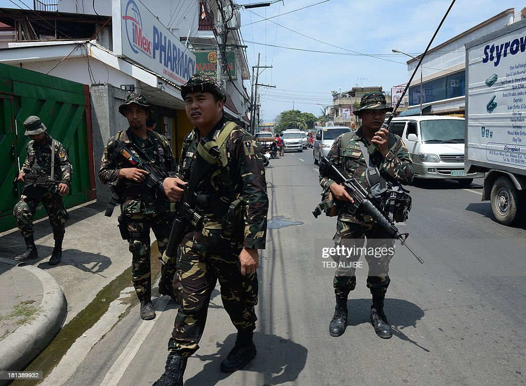 Philippine soldiers patrol streets as government forces clash anew with remnants of Muslim rebels in Zamboanga City, on southern island of Mindanao on September 21, 2013. Philippine security forces killed eight Muslim rebels September 19, as they hunted the remnants of a guerrilla force hiding in homes of a major city and believed to be holding hostages. AFP PHOTO/TED ALJIBE