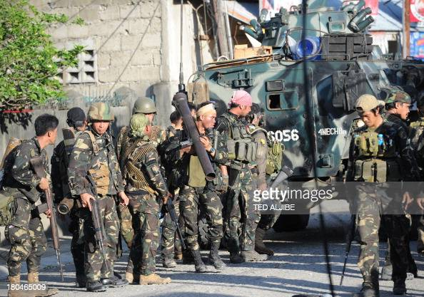 Philippine soldiers prepare to fall back after attempting an assault on Muslim rebel positions as the standoff enters its fifth day in Zamboanga City...